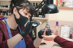 Manicurist in black latex gloves form the shape of a client`s nail in a beauty salon.  stock photos