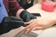 A manicurist in black latex gloves makes a manicure to a client using a manual electric milling machine in a beauty salon stock photos