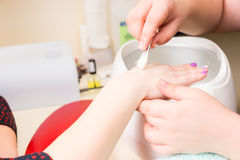 Manicurist Brushing Hand of Female Client. Close Up of Manicurist Brushing Hand of Female Client with Small White Bristled Brush Over Wax Warmer During Luxury Stock Images