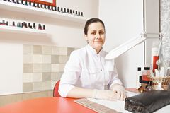Manicurist. Caucasian brunette manicurist sitting at the red desk in a parlor. Polish bottles in row on the wall racks. Horizontal shot Stock Photography