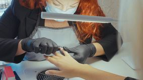Manicurist clear cuticle with professional nail tongs for manicure. Closeup finger nail care by manicure specialist in beauty salon. Red hair manicurist clear Stock Image