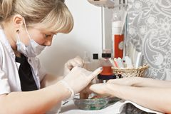 Manicure salon. Manicurist and client in manicure salon. Closeup horizontal shot Royalty Free Stock Image
