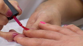 Manicurist Covers Nails With Red Nail Polish stock video footage