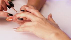 The manicurist covers the woman`s fingernail on the middle finger of her left hand with a brown varnish. Close-up stock video footage