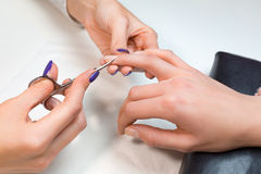 Manicurist cut clients cuticle with nail scissors Royalty Free Stock Photography