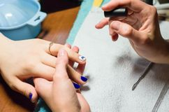 Manicurist doing manicure, painting nails with transparent nail polish. In salon on light towel Stock Photography