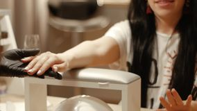 Manicurist examines client`s nails. A manicurist examines a client`s nails with a new nail polish at a beauty salon. Female manicure in a nail salon stock footage