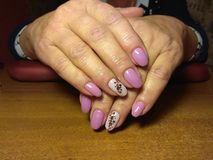 The manicurist excellently made her work a beautiful manicure with a polish gel on her hands and the client is happy Royalty Free Stock Photo