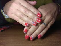 The manicurist excellently made her work a beautiful manicure with a polish gel on her hands and the client is happy Royalty Free Stock Photography