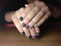 The manicurist excellently made her work a beautiful manicure with a polish gel on her hands and the client is happy Stock Image