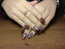 The manicurist excellently made her work a beautiful manicure with a polish gel on her hands and the client is happy Royalty Free Stock Image