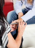 Manicurist Filing Client's Nail At Parlor Royalty Free Stock Photos