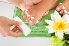 Manicurist filing a female nails Royalty Free Stock Image