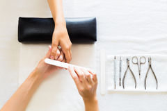 Manicurist Filing Finger Nails of a Woman Royalty Free Stock Photography