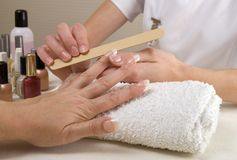 Manicurist filing womans nails Royalty Free Stock Images