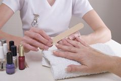 Manicurist filing womans nails Stock Photo