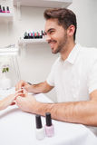 Manicurist giving customer a manicure Stock Images