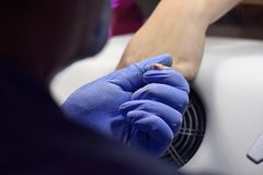 The manicurist grinded the nails of the girl in the nail salon a. Nd now gives them a fom Stock Photos