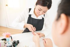 Manicurist hands cutting cuticle on nails Stock Photos