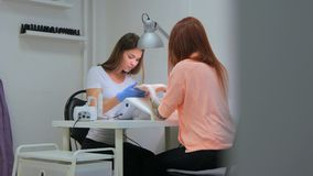 The manicurist holds hands of the client in beauty salon royalty free stock image