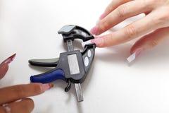 Manicurist make shape to enlarged acrylic nails Stock Photo