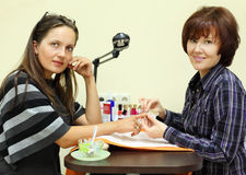 Manicurist makes manicure by nailfile for woman. Manicurist makes manicure by nailfile for women in beauty salon; two women look at camera Royalty Free Stock Photo