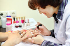 Manicurist makes manicure for woman by nail polish Royalty Free Stock Photography