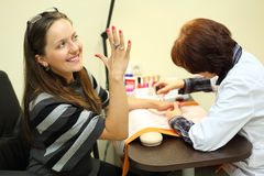 Manicurist makes manicure for woman by nail polish Stock Photos