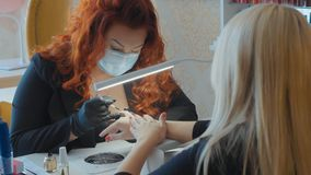 The procedure of painting nails. Manicure procedure in the beauty salon. Manicurist makes a procedure of painting nails her blond female client in red color Stock Image