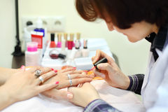 Manicurist manicures woman by pink nail polish Royalty Free Stock Image