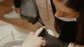 Cut the cuticle. A manicurist in a mask and protective gloves cuts the cuticle on the middle finger. Female nail cosmetologist makes manicure for woman in nail stock video footage