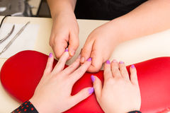 Manicurist Massaging Fingers of Client in Manicure. High Angle Close Up View of Esthetician Massaging Fingers of Female Client with Brightly Painted Finger Nails Royalty Free Stock Images