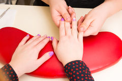 Manicurist Massaging Nail Beds of Female Client. High Angle Close Up of Manicurist Massaging Nail Beds on Hands of Female Client with Hands Resting on Red Pillow Royalty Free Stock Photo