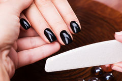 Manicurist master  makes manicure on woman's hands Royalty Free Stock Image