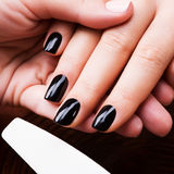 Manicurist master  makes manicure on woman's hands Stock Photo