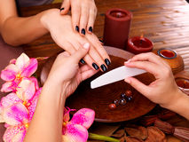Manicurist master  makes manicure on woman's hands. Spa treatment concept Royalty Free Stock Photography