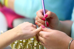 Manicurist master makes manicure on young woman hand.  Royalty Free Stock Photography