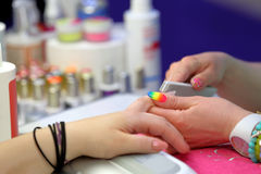 Manicurist master makes manicure on young woman hand Stock Images