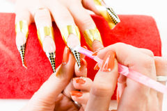 Manicurist master makes manicure on young woman hand Stock Photo