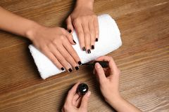 Manicurist painting client`s nails with polish in salon. Top view stock photography