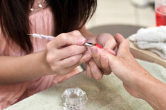 Manicurist painting customer's fingernails Royalty Free Stock Images