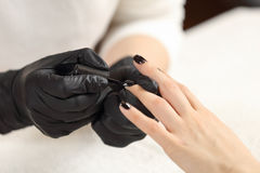 Manicurist paints customer nails in black Stock Photos