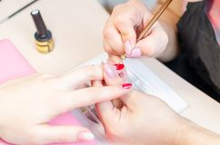 Manicurist paints nails with red lacquer in the salon.  stock photos