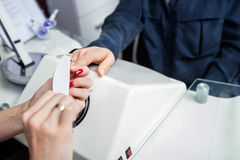 Manicurist Performing Manicure On Client's Hand At Beauty Parlor. Cropped image of manicurist performing manicure on client's hand at beauty parlor Royalty Free Stock Photo
