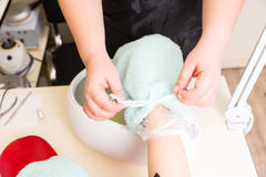Manicurist Performing Paraffin Wax Treatment. High Angle Close Up View of Manicurist Covering Gloved Hand with Terry Cloth Covering During Relaxing Paraffin Wax Royalty Free Stock Photo