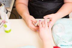 Manicurist Performing Paraffin Wax Treatment. High Angle Close Up View of Manicurist Peeling Dried Wax Layer from Hands of Female Client During Paraffin Wax Spa Stock Photos