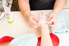 Manicurist Performing Paraffin Wax Treatment. High Angle Close Up View of Manicurist Peeling Dried Wax Layer from Hands of Female Client During Paraffin Wax Spa Stock Images