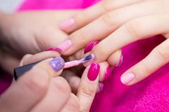 Free Manicurist Polish Nails On Women`s Hand In Nail Salon Stock Image - 140142841
