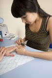 Manicurist polishing client's nails Stock Images