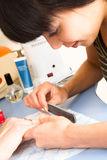 Manicurist polishing client's nails Royalty Free Stock Photo